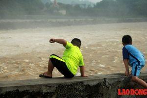 Trẻ con bất chấp nguy hiểm trèo lên thành lan can ngắm cảnh xả lũ như 'sóng thần'