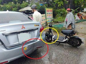 Vừa che ô vừa dùng điện thoại, lái xe đạp điện đâm vào đuôi ôtô