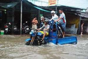 Đỉnh triều ở TP.HCM dân cấp tập chặn nước, ba gác trúng mánh nhờ 'cứu' xe
