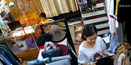 Nguoi phu nu dan canh de be trai trom iPhone 6 o shop quan ao - Anh 1