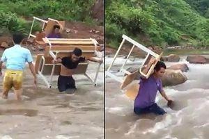 Thầy giáo còng lưng cõng bàn ghế vượt suối nước chảy siết ở Lai Châu