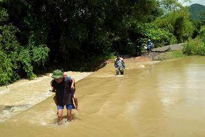Phụ huynh ở Nghệ An liều mình đưa con em đi học trong nước lũ chảy xiết